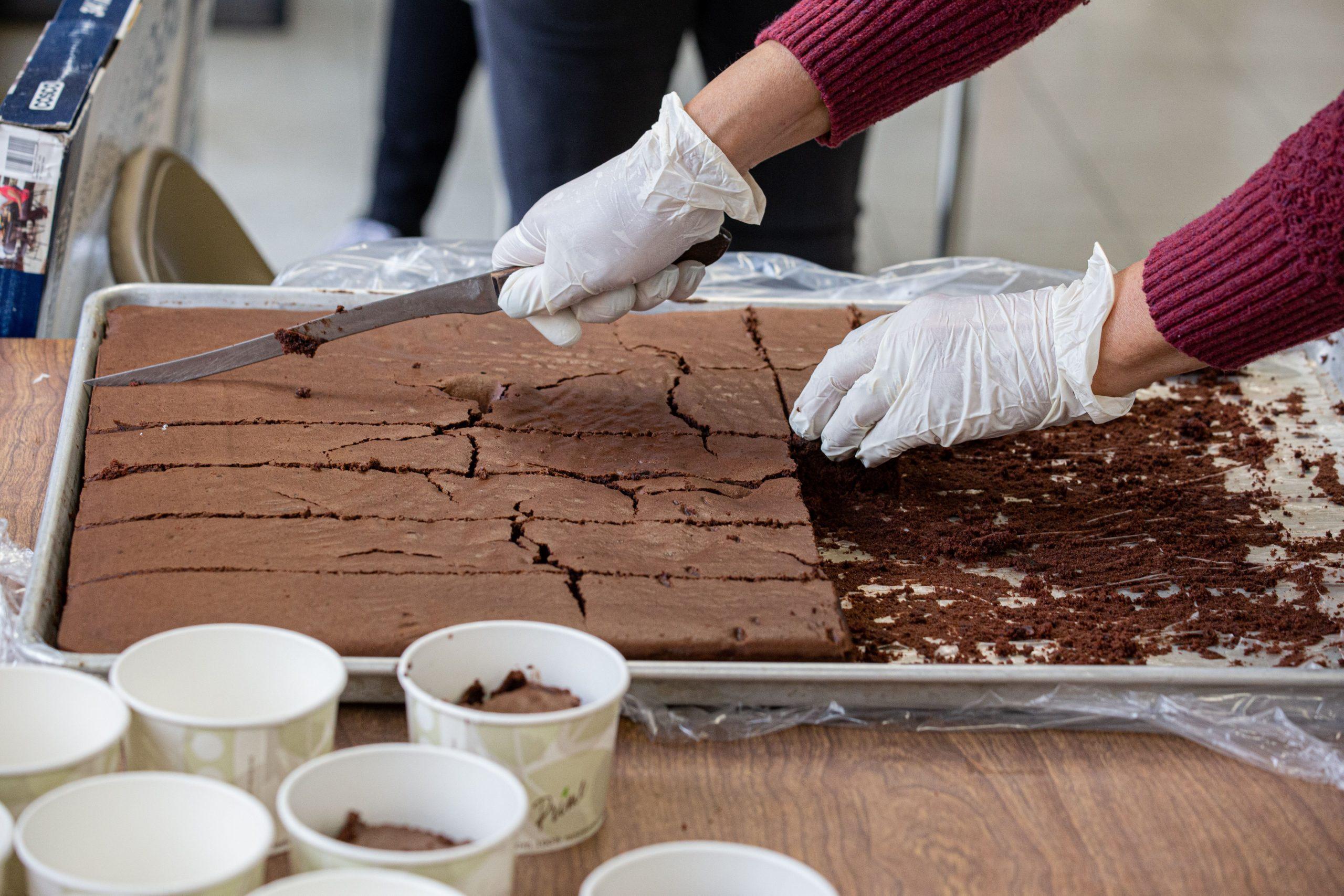 Volunteer cutting up brownies