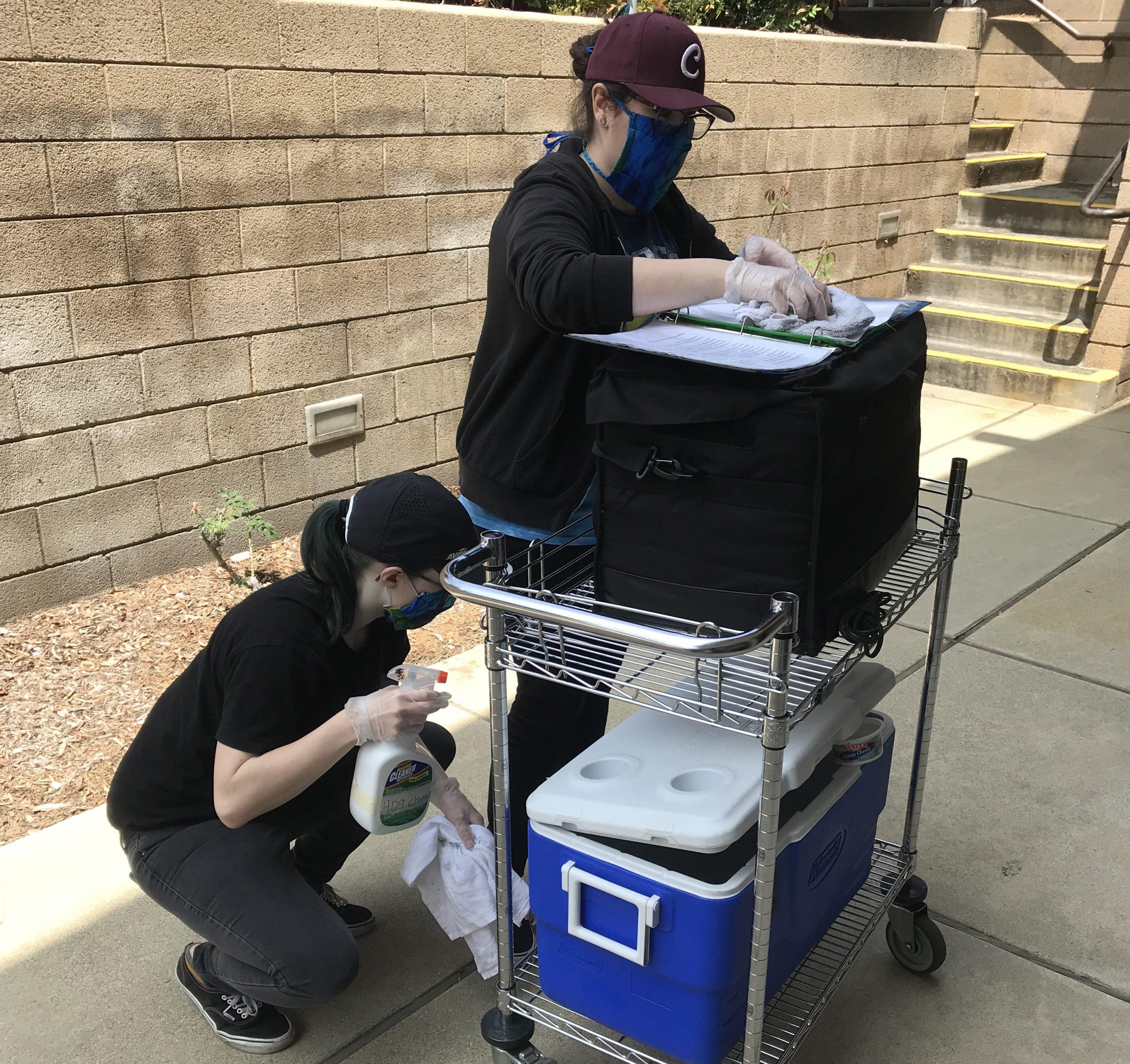 Volunteers sanitizing cooler and bag