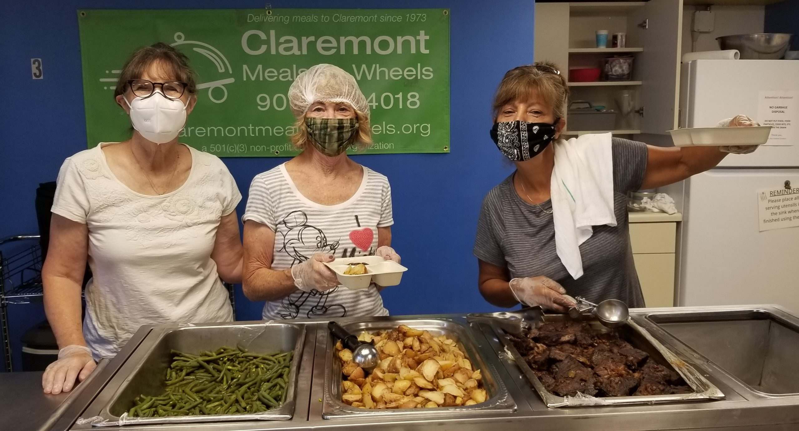 Packers wearing masks and holding up hot meals